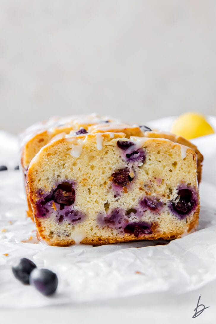 lemon blueberry bread slice leaning up against loaf showing blueberries inside and glaze dripping down the top