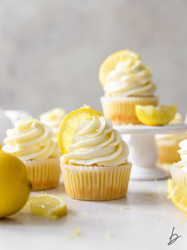 lemon cupcakes with frosting and lemon wedges as garnish
