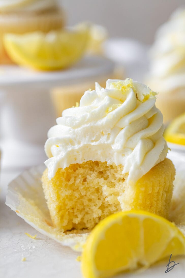 bite taken out of lemon cupcake sitting on top of paper cupcake liner with lemon slice in front