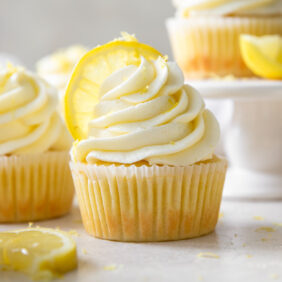lemon cupcake topped with lemon buttercream frosting and a lemon slice next to more cupcakes and a lemon