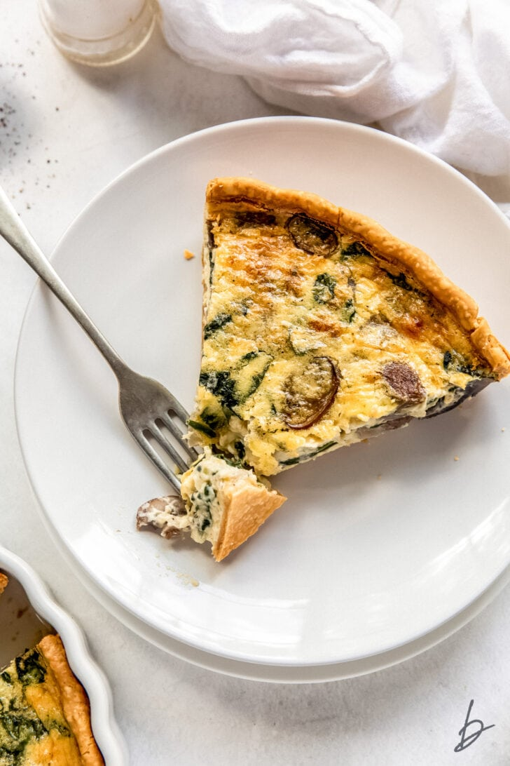 slice of spinach mushroom quiche ona plate with fork taking a bite