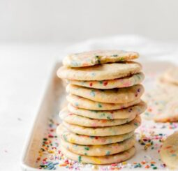 tall stack of sprinkle sugar cookies on a cookie sheet with more sprinkles