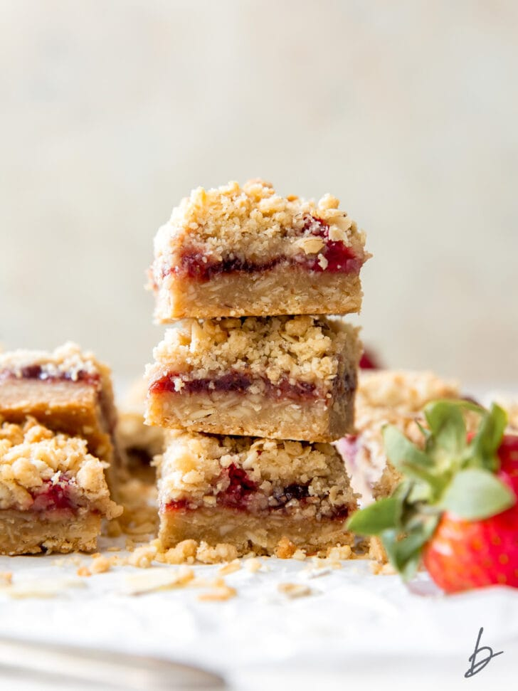 stack of three strawberry oatmeal bars showing layers of crust, strawberry preserves and oatmeal crumble topping