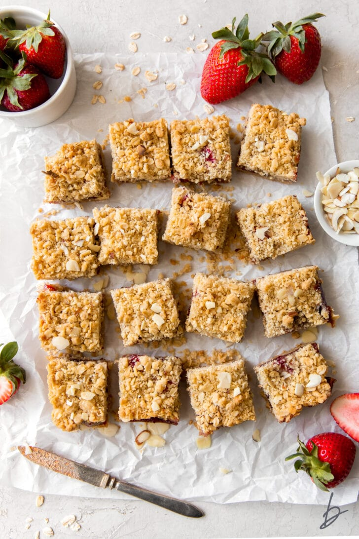 strawberry oatmeal bars cut into squares on parchment paper next to fresh strawberries