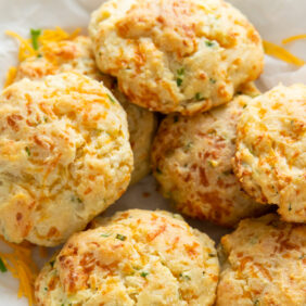 cheddar biscuits in a pile on crinkled parchment paper