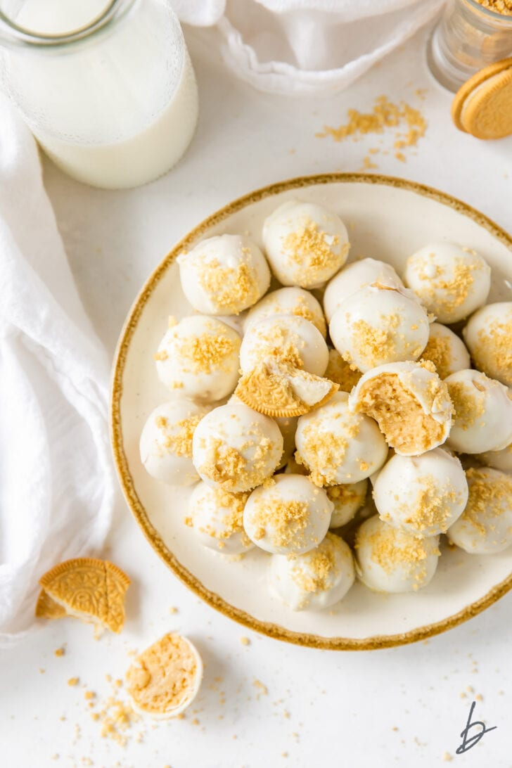 white chocolate covered golden oreo truffles on gold rimmed white plate next to glass bottle of milk