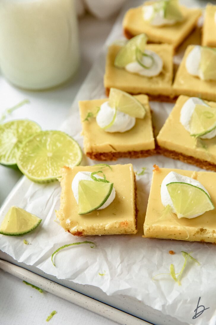 key lime pie bars on crinkled wax paper next to lime slices