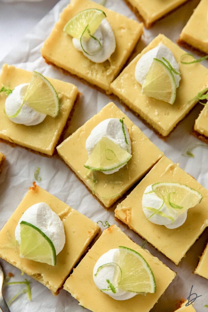 tops of key lime pie bars garnished with whipped cream and lime slices