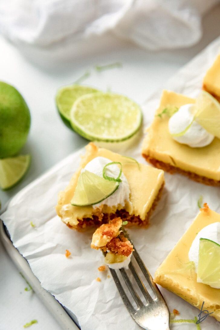 fork taking bite of key lime pie bars with graham cracker crust