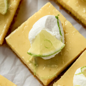 key lime pie square garnished with whipped cream and lime slice