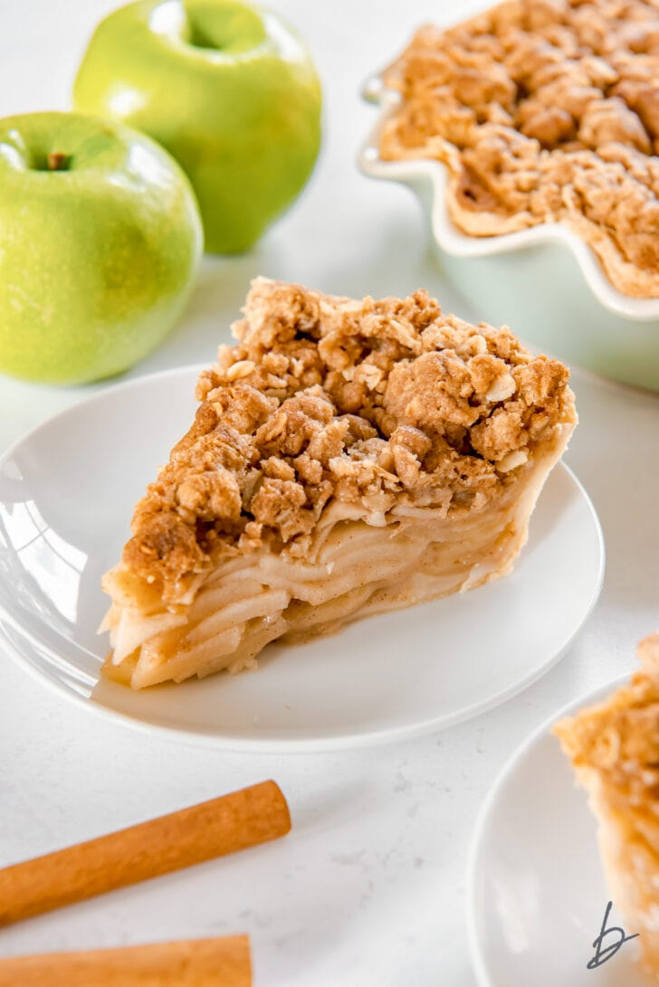 slice of apple crumble pie on white round plate in front of granny smith apples and cinnamon sticks