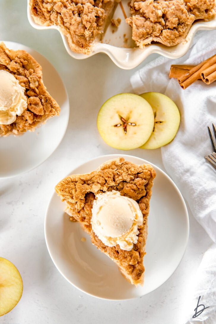 apple crumble pie slice topped with scoop of vanilla ice cream on white round plate next to apple slices and cinnamon sticks
