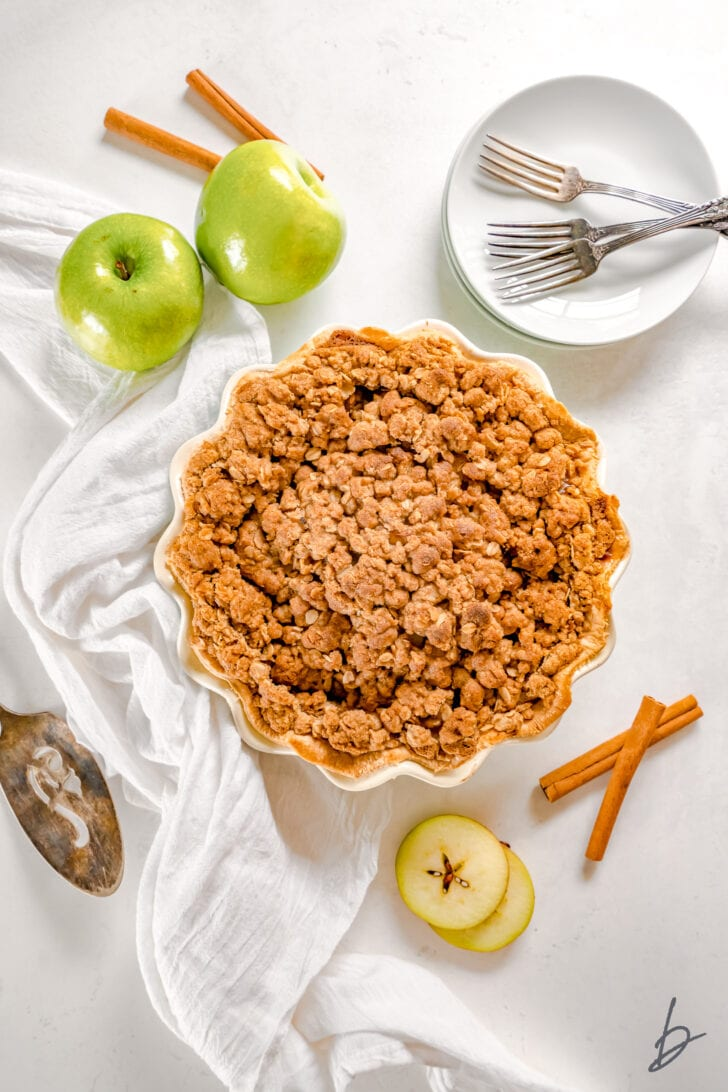 apple crumble pie in a pie dish next to white kitchen cloth, granny smith apples and cinnamon sticks