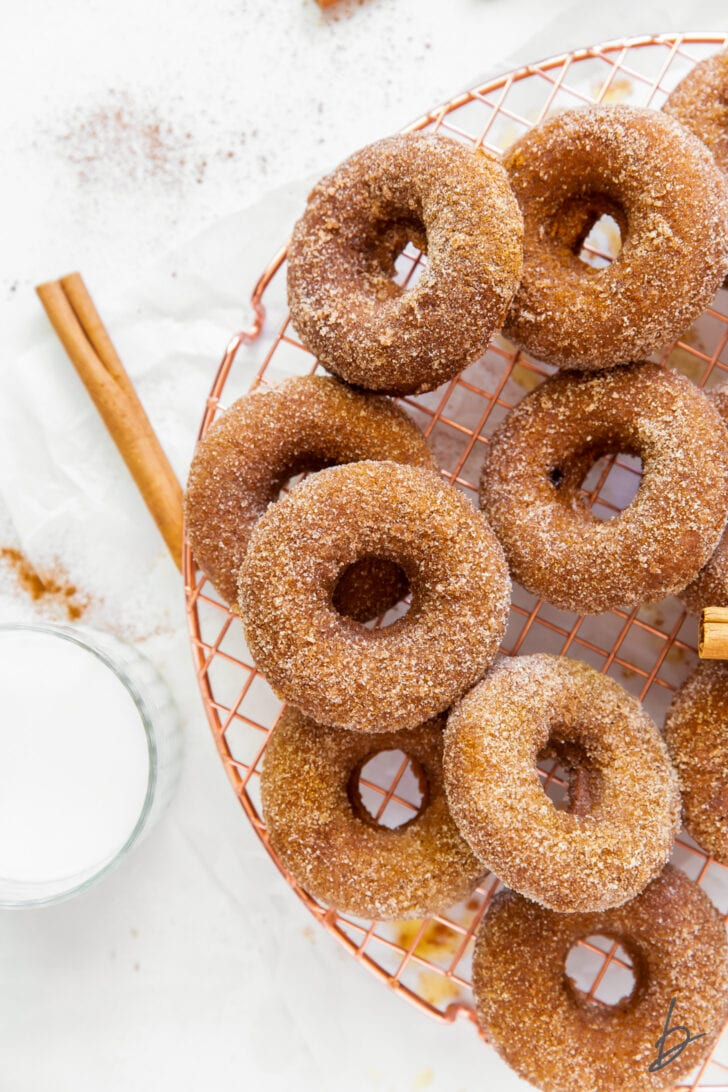 cinnamon sugar coated baked pumpkin donuts on round copper wire cooling rack next to cinnamon stick