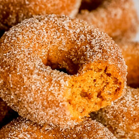 pumpkin donut with a bite taken out on top of pile of more donuts covered in cinnamon sugar