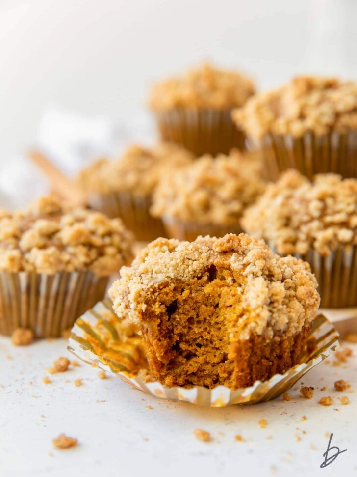 pumpkin muffin with a bite sitting on open paper liner with more muffins behind it