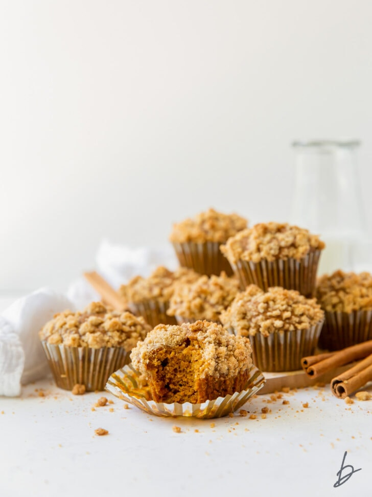 pumpkin muffin with streusel on open paper liner with more muffins piled in the background