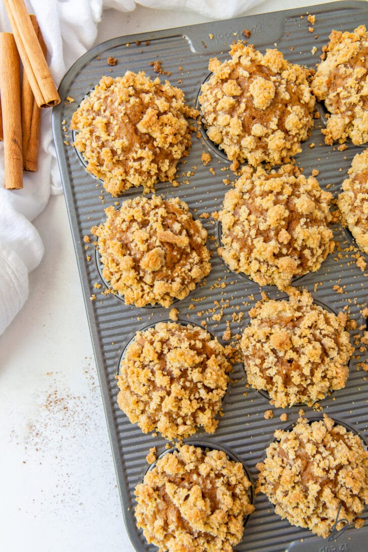pumpkin muffins in pan with streusel topping on muffins and pan