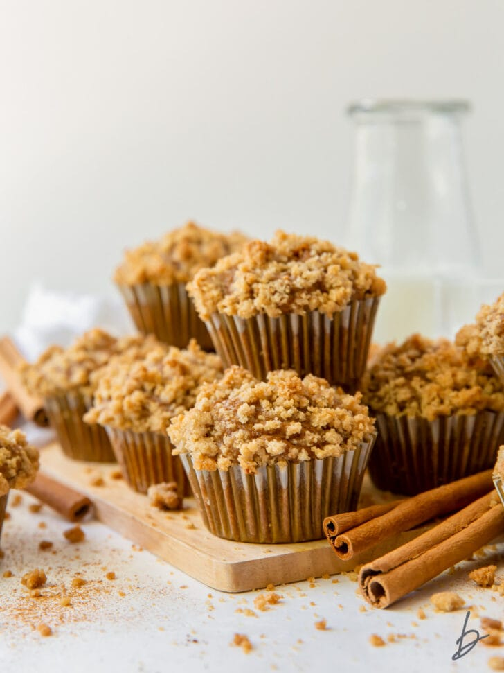 pumpkin muffins with streusel in pile on small wood cutting board next to cinnamon sticks