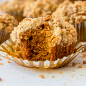pumpkin muffin with a bite taken out on top of a paper liner