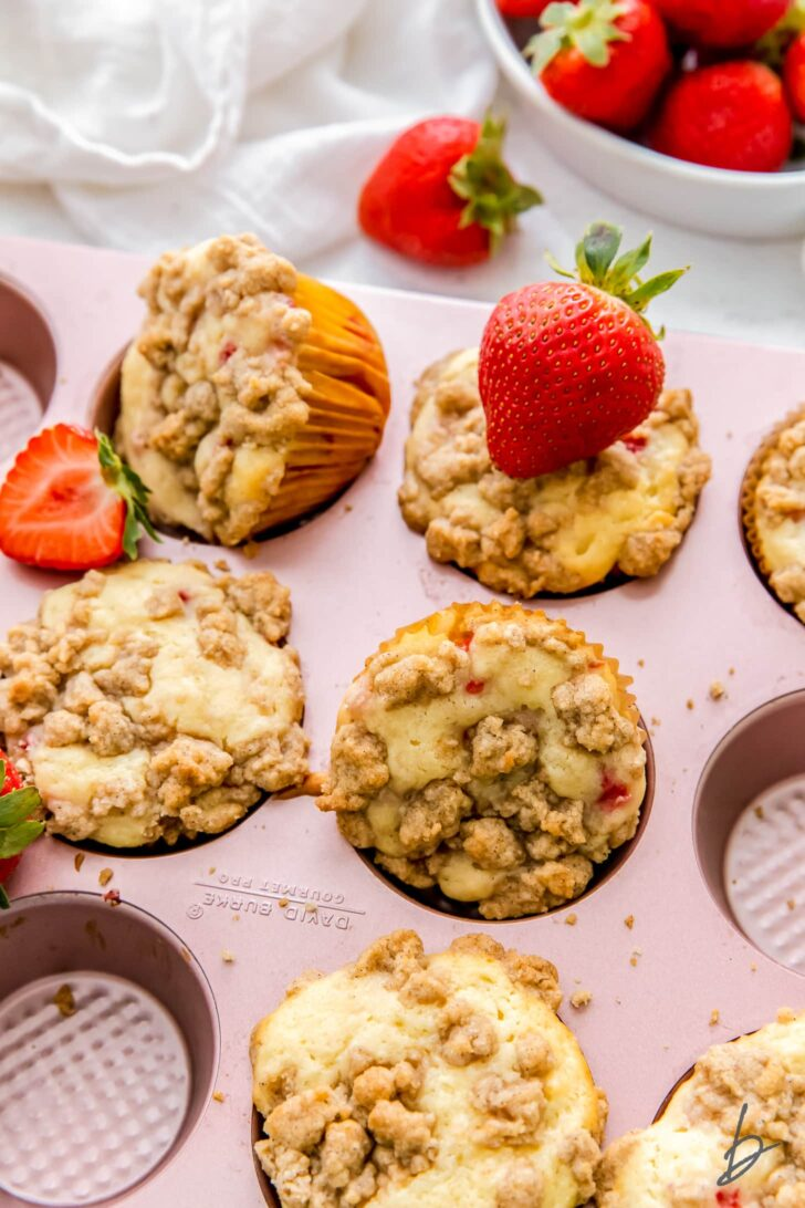 strawberry muffins with streusel topping in pink muffin pan