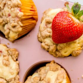 strawberry muffins with streusel topping in a pink muffin with