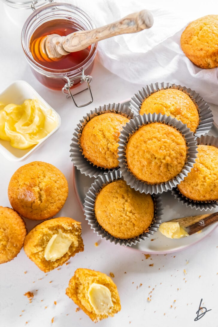 honey jar next to plate of cornbread muffins and a cornbread muffin cut in half with butter