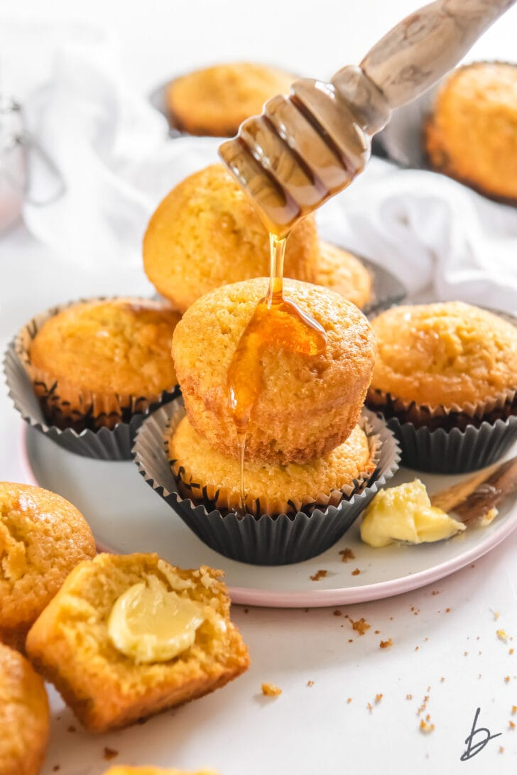 honey being drizzled on top of two cornbread muffins stacked on plate with more muffins