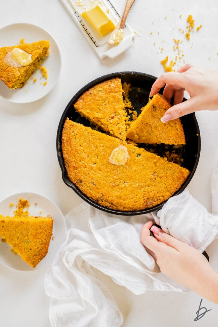 hand picking up slice of jalapeno cheese cornbread from a skillet with two plates with cornbread next to skillet