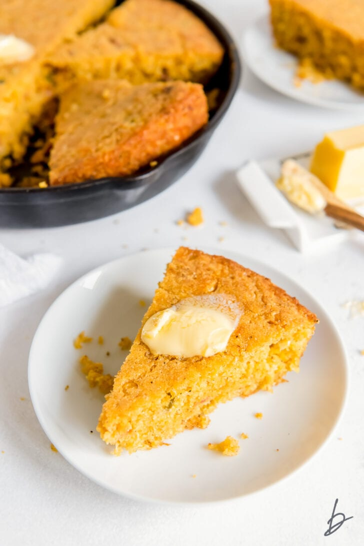 white round plate with triangle slice slice of jalapeno cornbread with melted butter on top