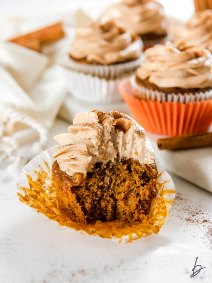 open paper liner with pumpkin cupcake with a bite taken out of it