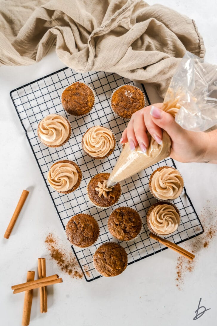 hand holding frosting bag and frosting pumpkin cupcakes on wire cooling rack