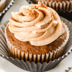 pumpkin cupcake with cinnamon cream cheese frosting on open paper liner