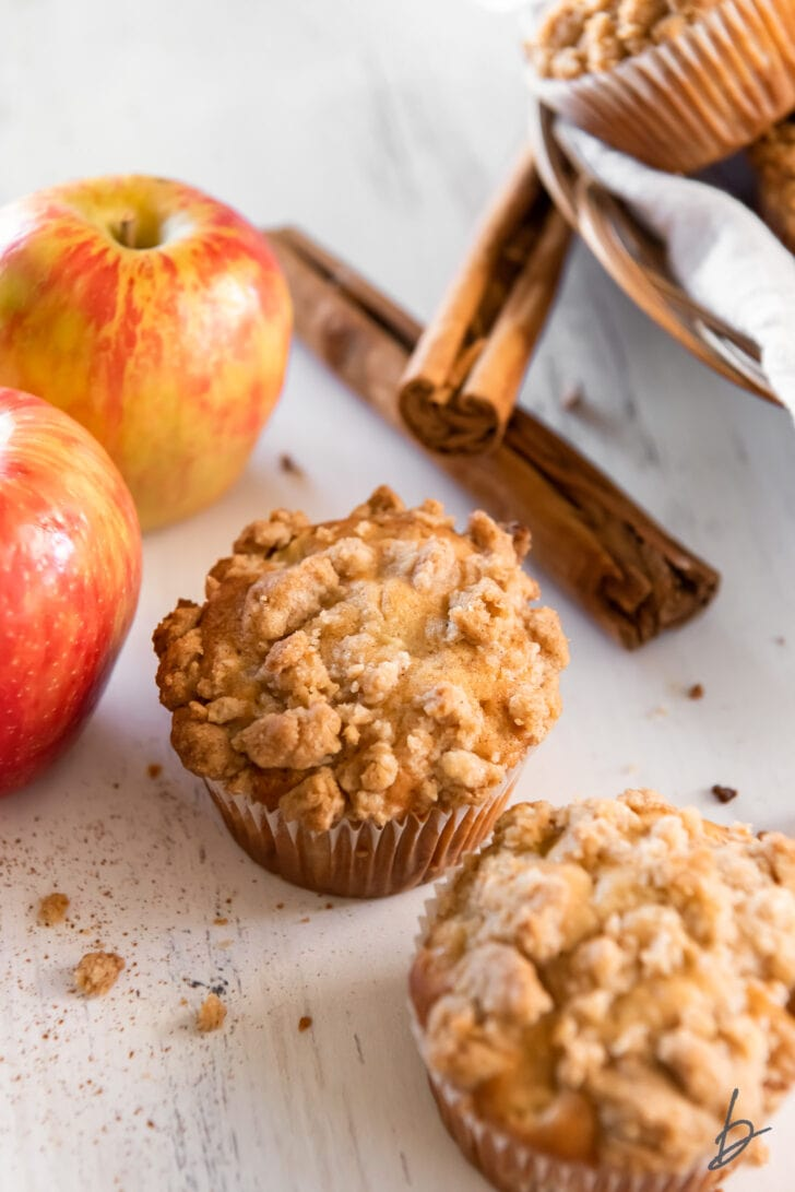 two apple crumble muffins next to two apples and cinnamon sticks