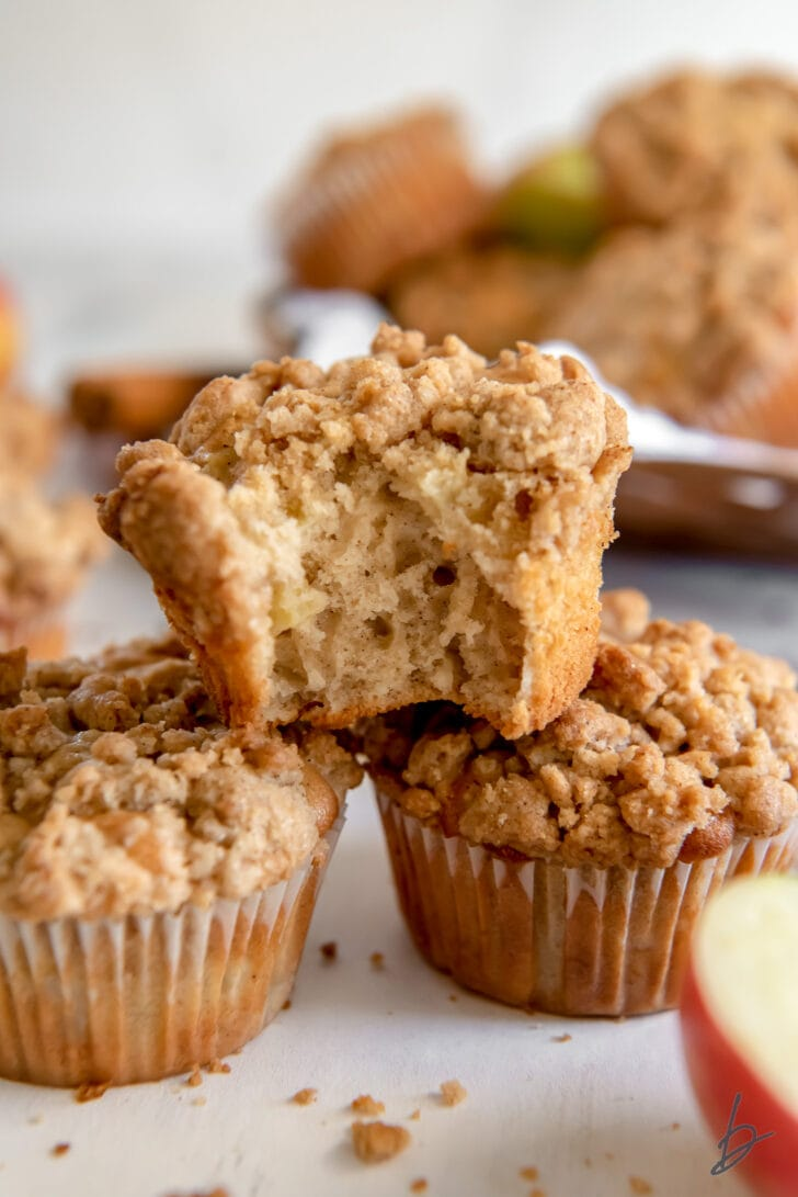 apple crumble muffin with a bite on top of two other muffins