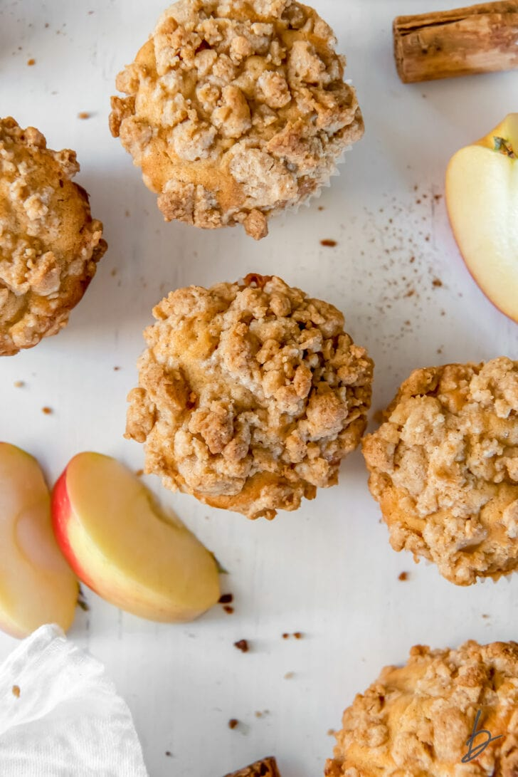 tops of apple crumble muffins on surface next to apple slices and cinnamon stick
