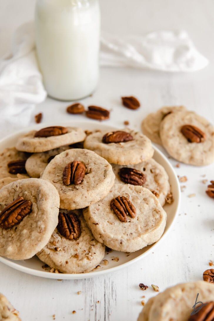 plate of pecan sandies cookies in front of a glass milk bottle