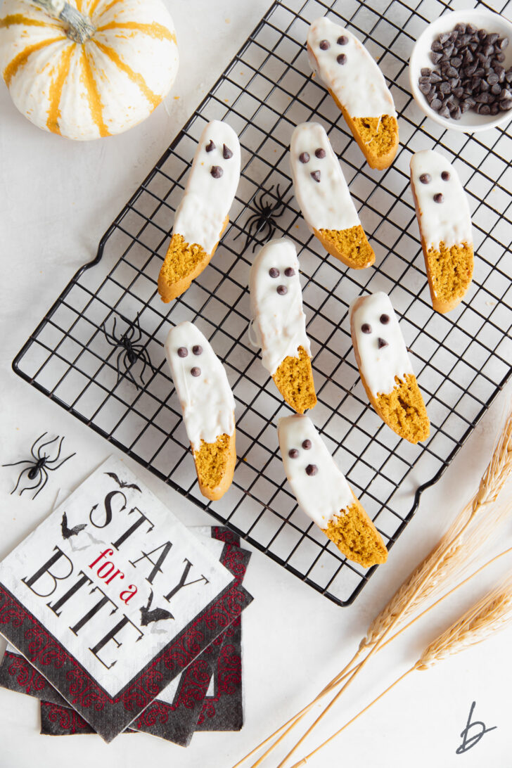 white chocolate dipped pumpkin biscotti that look like ghosts on black wire cooling rack next to halloween napkin and mini pumpkin