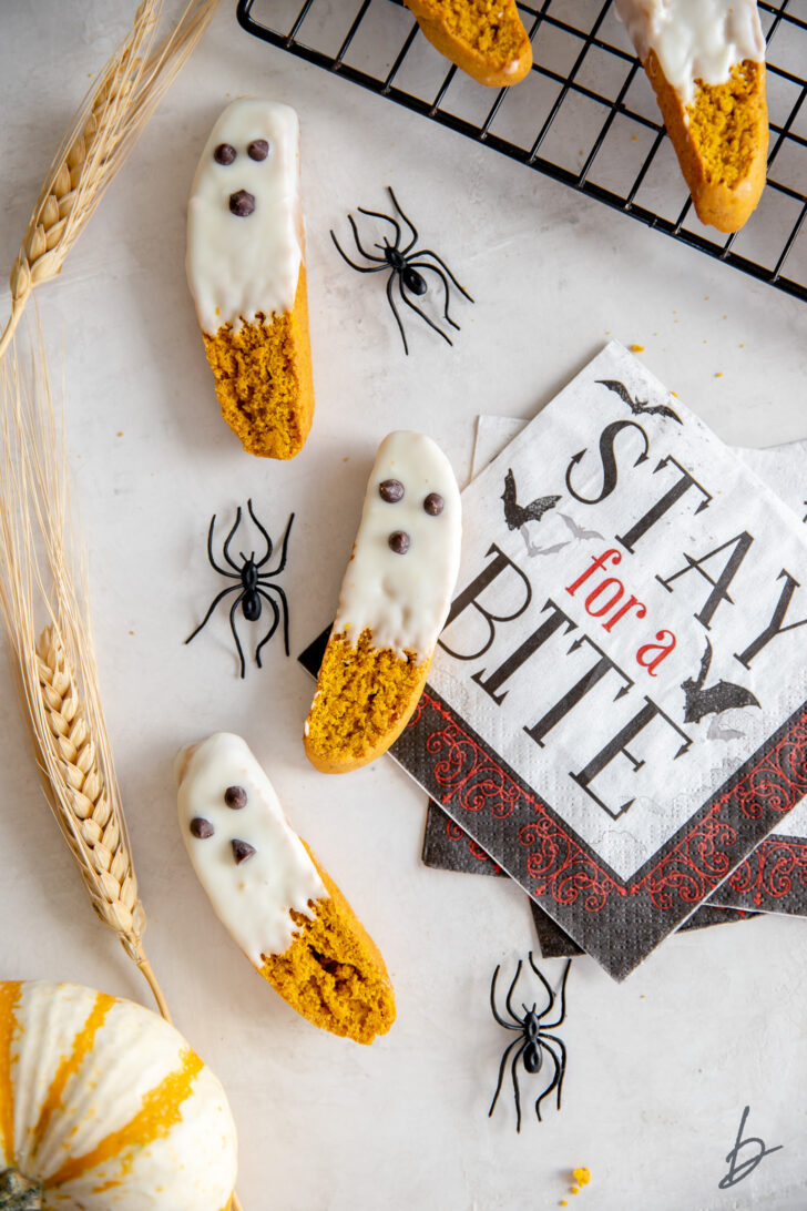 three white chocolate dipped pumpkin biscotti that look like ghosts next to fake spiders and halloween napkin