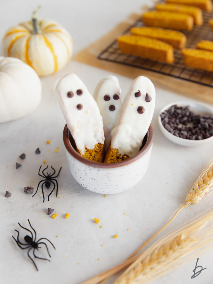 a cup with three white chocolate dipped pumpkin biscotti decorated to look like ghosts