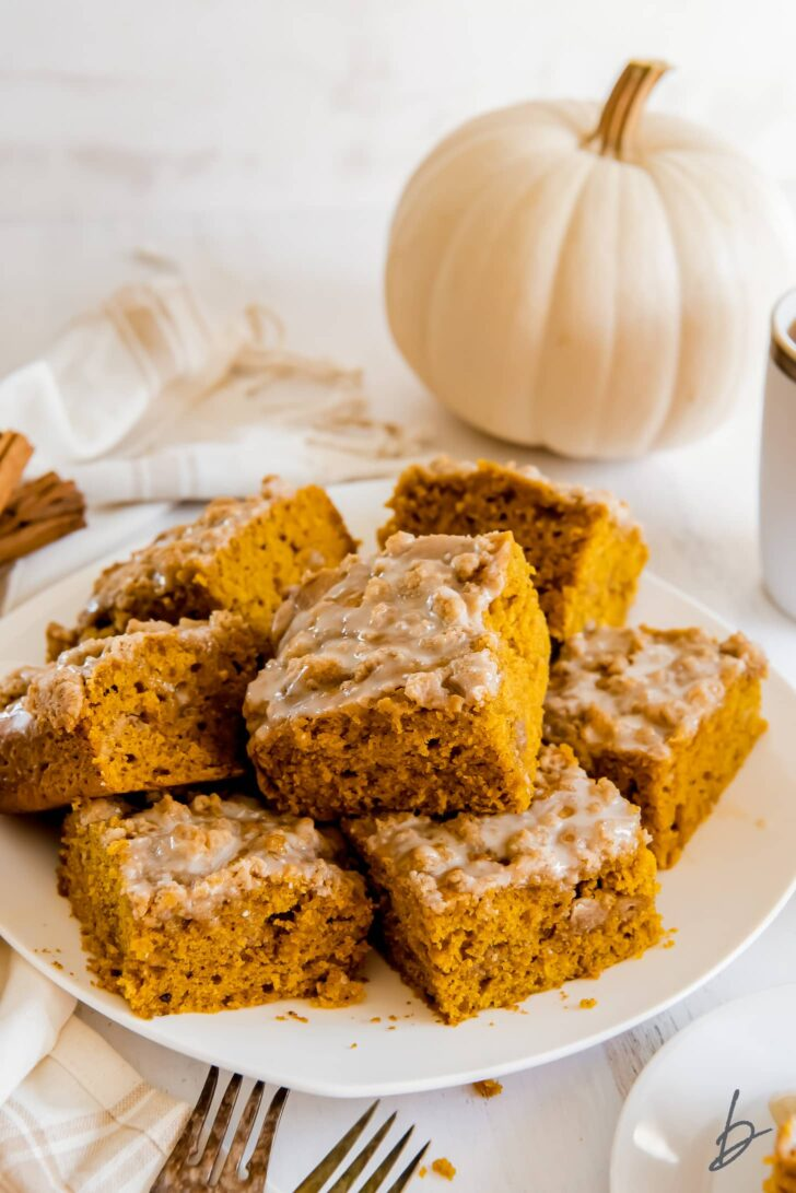 plate of pumpkin coffee cake square with icing and white pumpkin behind plate