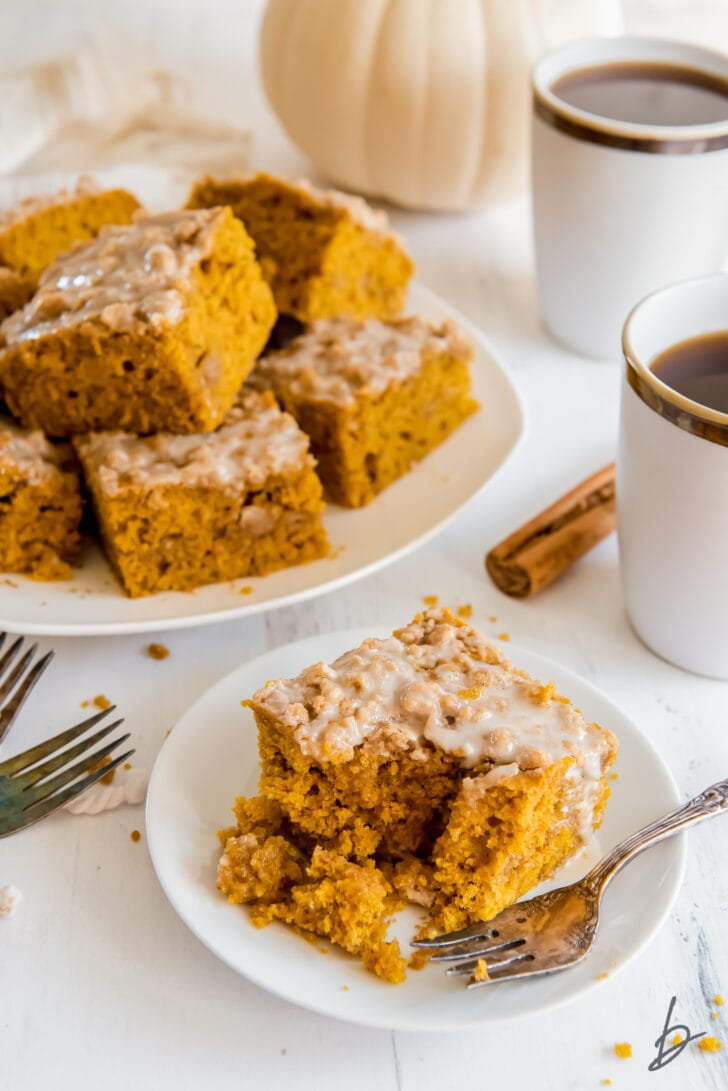 fork taking bite of pumpkin coffee cake on small white plate with larger plate with more coffee cake behind it