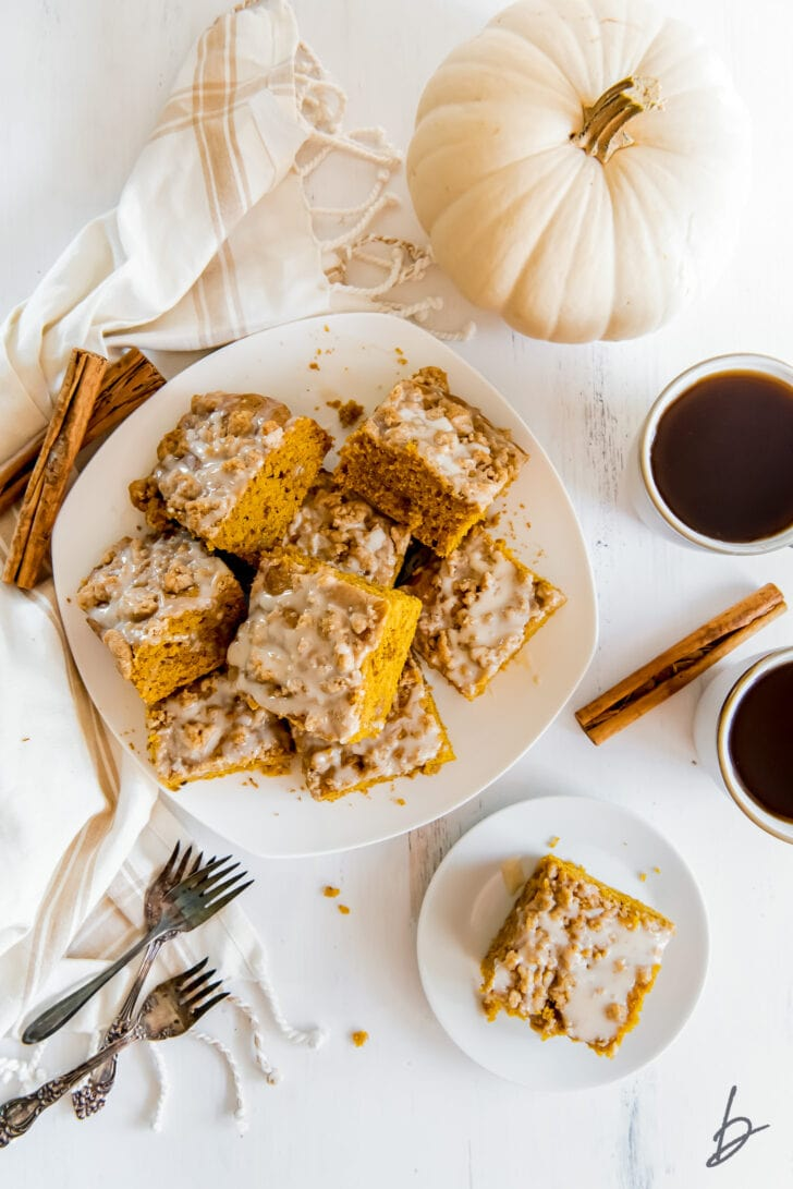 pumpkin coffee cake squares on white round plate next to white pumpkin and mugs of coffee