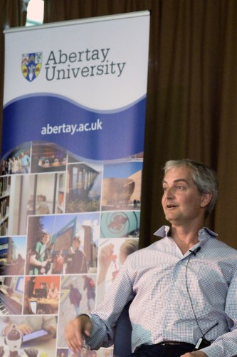 Ed Fries seated onstage with an Abertay University banner behind him