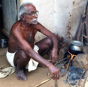 old man cooking outside hut