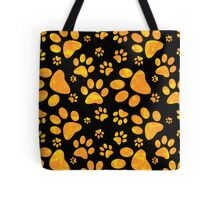 Yellow Gold Pet Paw Prints Tote Bags. Paw prints in a yellow / orange gold as a seamless pattern. Great for animal lovers such as dogs, cats and any animals who has paws.