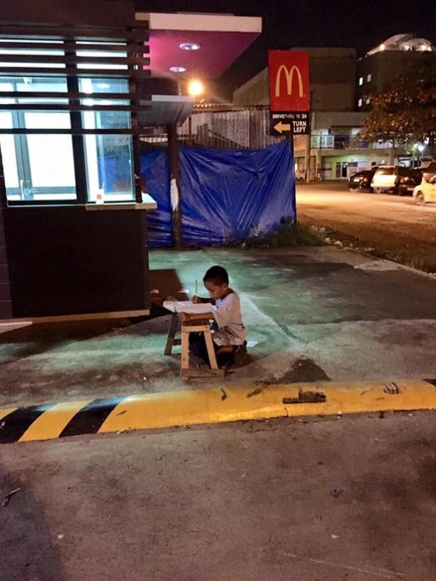 мальчик делает уроки на улице