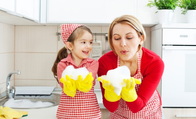 Mother and daughter having fun blowing foam in the kitchen