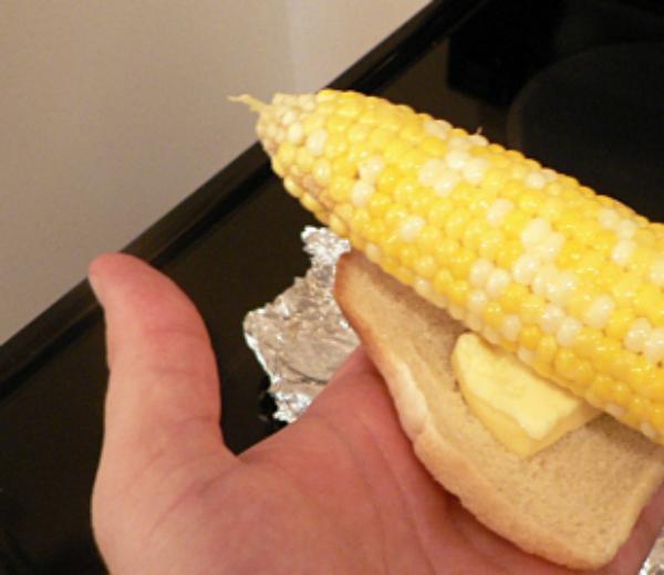 Чтобы удобно помазать горячую кукурузу маслом, положите его на кусочек хлеба. Кстати, после этого хлеб будет очень вкусным