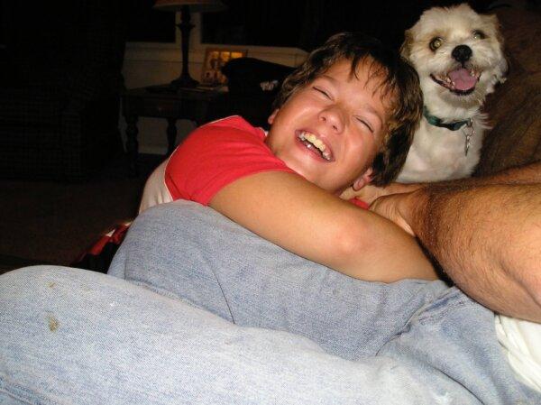 Boy Hugging Small Dog